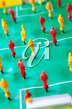 Macro shoot of red and yellow players of tabletop football game.