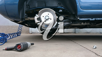 View of a car disc brake and pneumatic air screwdriver on the ground during tyre replacement. Car maintenance.