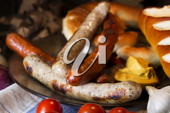 Bavarian White And Red Sausages With Mustard, Bavarian Buns and Pretzels At The Table. October Fest Concept
