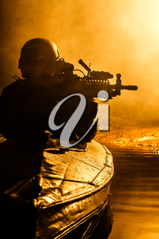 Backlit silhouette of special forces marine operators in military kayak on fire explosion background. Battle operation