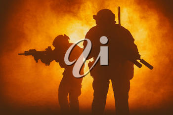 Black silhouettes of pair of soldiers in smoke moving through fire burning in battle operation, sacrificing their lives of our security. Back light