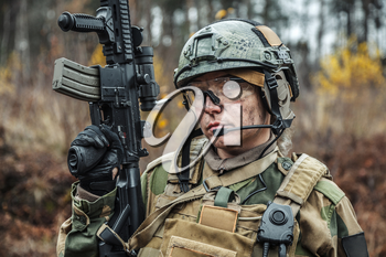 Norwegian Armed Forces Special Command FSK female soldier closeup portrait. Protective eye-wear and assault gun