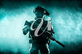 Army soldier in Combat Uniforms with assault rifle, plate carrier and combat helmet are on, Shemagh Kufiya scarf on his neck. Studio contour silhouette shot, backlight, dark glowing smoke background