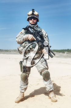 Portrait of United states airborne infantry corporal with arms, camo uniforms dress. Combat helmet on, tactical light, boots and kneepads, front view