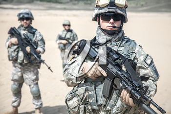 United states airborne infantry men with arms, camo uniforms dress. Front view, two militants are defocus