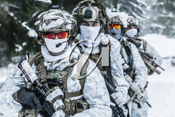 Winter arctic mountains warfare. Action in cold conditions. Squad of soldiers with weapons in forest somewhere above the Arctic Circle