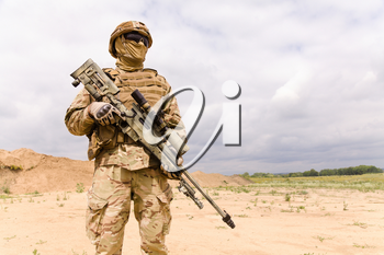 Equipped and armed special forces soldie in the desert, copy space fo text.