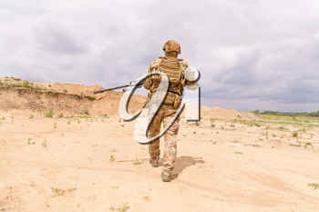 Special force soldier in camouflage with rifle walks across desert