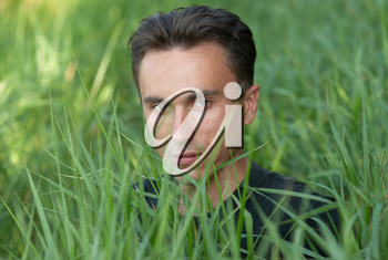 Man's portrait in the green grass background