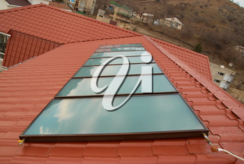 Solar water heating system (geliosystem) on the red house roof.
