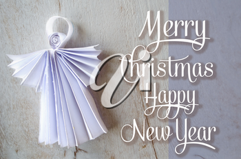 Xmas postcard with hand made paper angel and congratulation. Happy New Year and Merry Christmas greeting card with angel on wooden background. Holidays template.