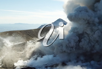 Smoke from the mouth of the volcano. Eruption. Clubs of smoke and ash in the atmosphere.