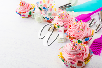 Decorated pink birthday cupcakes  and cookware. Birthday homemade cupcakes decorating process. 