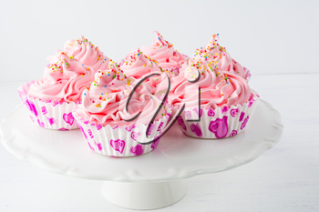 Decorated pink birthday cupcakes  on the cake stand. Sweet dessert  pastry with whipped cream. Birthday homemade cupcakes served for party.