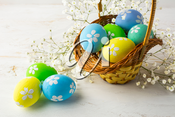 Hand-painted decorated Easter eggs in the basket with small white baby's breath flowers on a white wooden background, close up