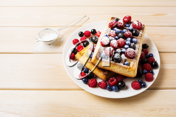 Belgian waffles with blueberry, raspberry and ising sugar. Breakfast soft waffles with fresh berries.