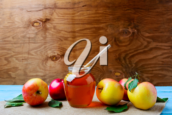 Glass honey jar with dipper and fresh apples, copy space. Rosh hashanah concept. Jewesh new year symbols.