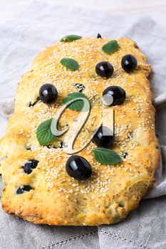 Italian bread with olive, garlic and herbs. Homemade traditional Italian bread focaccia on the linen napkin.