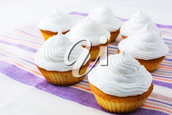 Sweet cupcakes with white whipped cream . Homemade cupcakes with whipped cream.  Sweet gourmet pastry dessert. Homemade cupcakes served for party.