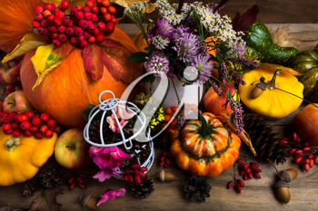 Thanksgiving arrangement with orange pumprin, yellow, green, turban squash, white birdcage, cones, apples and purple clower flowers, top view