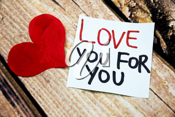 Emotional handwritten messages about love with red heart symbol above wooden retro background. Flat lay image above Love you handwritten emotional messages.