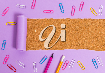 Stationary and torn cardboard placed above a wooden classic table backdrop