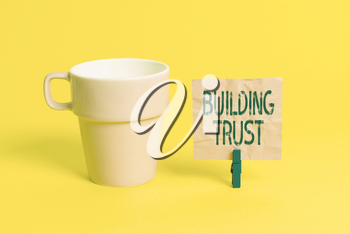 Text sign showing Building Trust. Business photo showcasing activity of emerging trust between showing to work effectively Cup empty paper blue clothespin rectangle shaped reminder yellow office