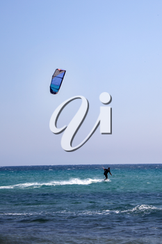 A black vested kitesurfer is using  blue coloured inflatable kite on relatively quite turqouise sea. Inflatable kites are popular in many year in kite surfing because of its reliability.