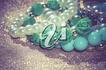 Stylish fashion bracelets with blue beads and pearls on glittering background.