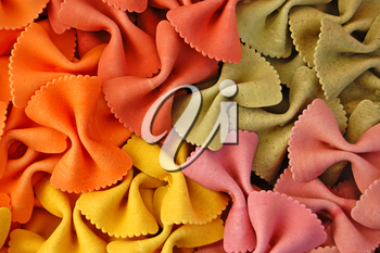 Four different flavors of farfalle bow ties pasta. Italian food background detail.