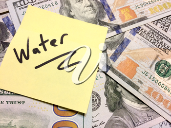 American cash money and yellow post it note with text Water in black color aerial view