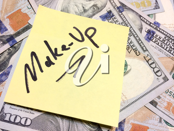 American cash money and yellow sticky note with text Make-up in black color aerial view