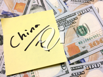 American cash money and yellow sticky note with text China with question mark in black color aerial view