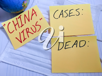 China virus Coronavirus COVID-19 infection medical cases and deaths. COVID respiratory disease influenza statistics hand written on surgical mask and earth globe background