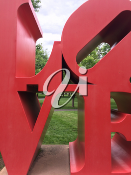 Love art text in big red metal letters in park with grass