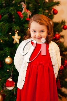 Portrait of a beautiful little child with red dress near Christmas tree.