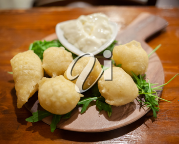 Coccoli is an appetizer from Italy. Pizza dough balls are fried and sprinkled with salt, served cheese.