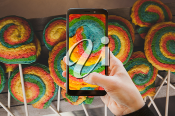Using the camera with a mobile phone. Colorful pastry shaped like a pinwheel.