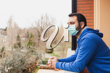 Young caucasian man with mask looking out onto home terrace during quarantine due to coronavirus covid19 pandemic.