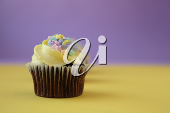 Easter yellow and lilac chocolate cupcake with candies on a yellow and purple background
